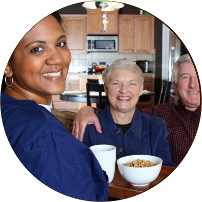 caregiver with an elderly couple smiling